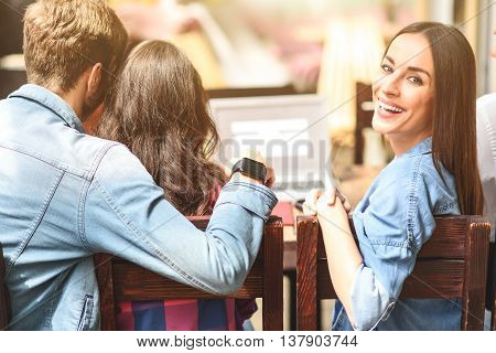 Relaxing at local coffee shop. Portrait of smiling woman spending some time with her friends in coffee shop