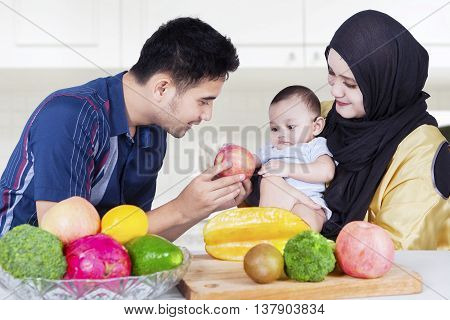 Portrait of healthy family with fresh fruits in the kitchen man giving apple fruit to his son