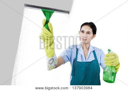 Portrait of maid woman washing the window with cleaning tools isolated on white background