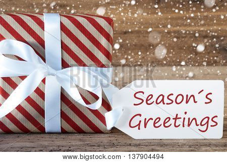 Christmas Gift Or Present On Wooden Background With Snowflakes. Card For Seasons Greetings. White Ribbon With Bow. English Text Seasons Greetings