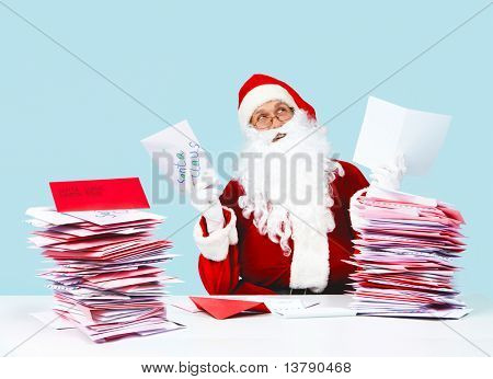 Portrait of inspired Santa Claus holding letters and looking upwards
