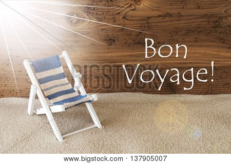 Sunny Summer Greeting Card With Sand And Aged Wooden Background. French Text Bon Voyage Means Good Trip. Deck Chair For Holiday Or Vacation Feeling.