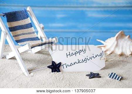 Summer Label With English Text Happy Thanksgiving. Blue Wooden Background. Card With Holiday Greetings. Beach Vacation Symbolized By Sand, Deck Chair And Shell.
