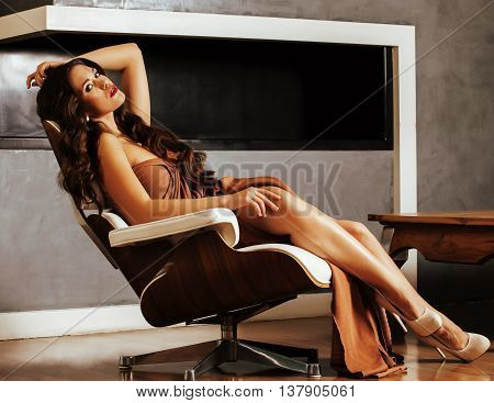 beauty yong brunette woman sitting near fireplace at home, winter warm evening in interior, waiting to celebrate wooden