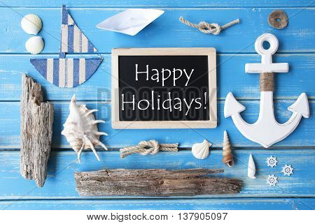 Flat Lay Of Chalkboard On Blue Wooden Background. Nautic Or Maritime Summer Decoration As Holiday Greeting Card. English Text Happy Holidays