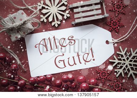 Nostalgic Christmas Decoration Like Gift Or Present, Sleigh. Card For Seasons Greetings With Red Paper Background. German Text Alles Gute Means Best Wishes