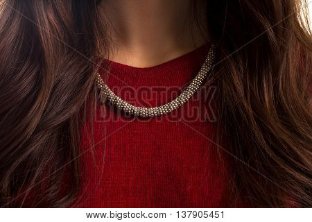 Accessory on lady's neck. Red garment and necklace. Custom made jewelry of silver. Precious metal and quality fabric.