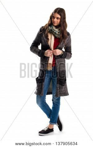 Lady in dark sweater coat. Printed scarf and denim pants. Woolen outerwear for autumn. Model wears new garment.