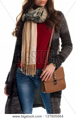 Girl in dark sweater coat. Printed scarf and brown handbag. Warm clothes and stylish accessory. Spring outfit with blue jeans.