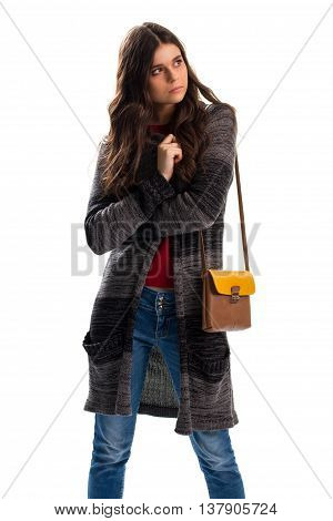 Young lady in sweater coat. Two-tone bag and jeans. Spring apparel from lookbook. Comfortable and warm outerwear.