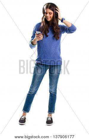 Girl in headphones is smiling. Woman with cell phone. Turn on your favorite song. Smartphone with media player.