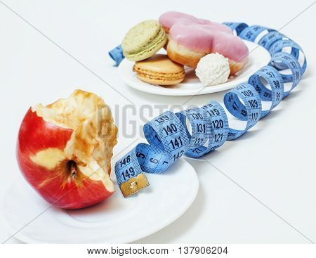 new diet concept, question sign in shape of measurment tape between red apple and donut isolated on white, noone