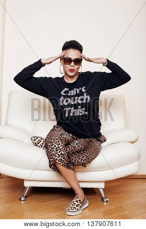 pretty stylish african american big mama woman well dressed. swag relax at home, leopard print on clothers. fashion look sunglasses