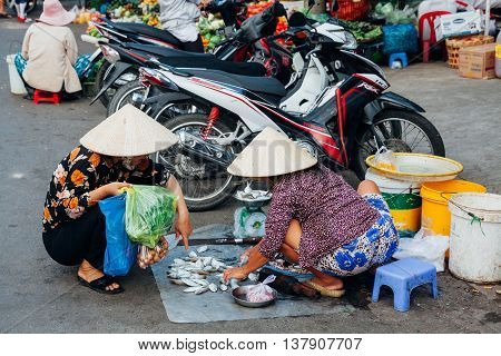 NHA TRANG VIETNAM - JANUARY 20: Vietnamese woman in traditional conical hat is selling fish at the wet market on January 20 2016 in Nha Trang Vietnam.
