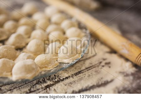 Raw homemade russian food - dumpling. They are in flour and have traditional form. Placed on the plate. Pork chicken mincemeat. Background table in kitchen. Wooden plunge.