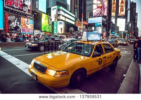 NEW YORK CITY - MAY 12: Yellow cab on Times Square traffic and animated LED signs is a symbol of New York City and the United States May 12 2016 in Manhattan New York City. USA.