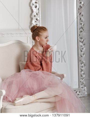 Pretty young ballerina drinking coffee sitting on a chair. Ballerina in tutu and pink sweater
