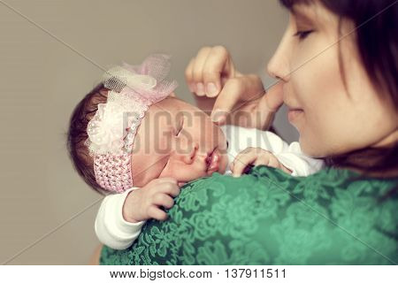 Young Asian mother holding the shoulder of the baby which is sleeping and gently strokes her cheek with a finger