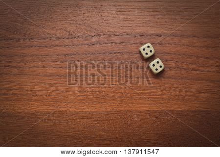 two dice number double 4 on the wooden table