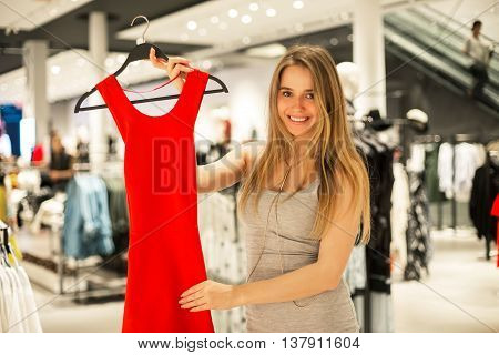 Beautiful happy girl doing shopping and fitting red dress in the store