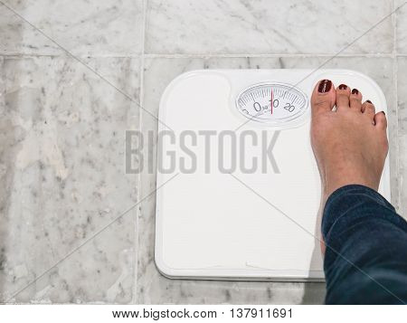 the girl weigh her body by wieght scale