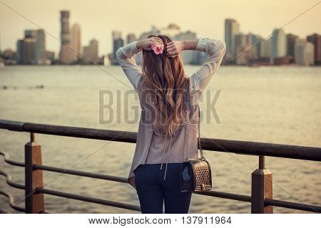 Beautiful woman standing on city embankment and enjoying the view