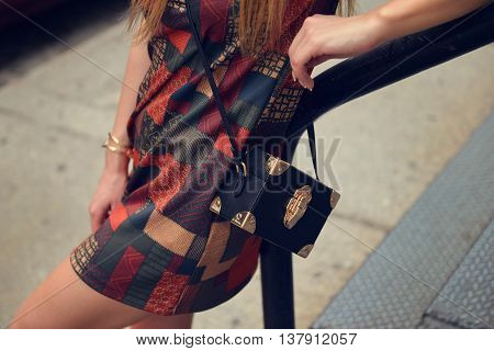 Beautiful women`s outfit with short elegant dress and black leather luxury bag