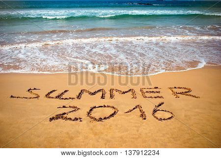 Inscription on wet sand Summer 2016. Concept photo of summer vacation.