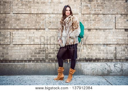 Beautiful tourist woman standing near the wall with backpack wearing fur coat
