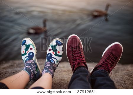 Feets with shoes of the couple on romantic date sitting on the rocks near lake