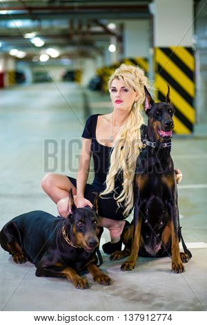 Blonde in a black dress crouched in an embrace with two Doberman on leashes in the underground parking