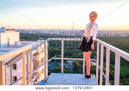 Girl with beautiful long blond hair in a white blouse and short skirt is standing on a fire escape on the roof