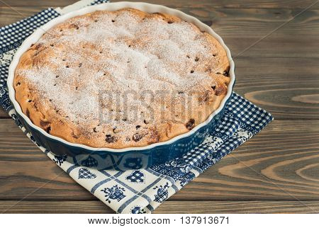 A cake with cherries and blueberries on wooden background.