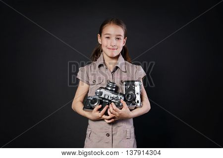 Little cute girl pose with heap of old vintage film cameras at black background. Small child photographer happy and smiling, studio portrait. Collecting antiques, old things