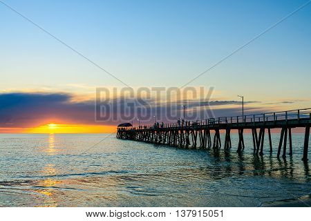 People walking along the Henley beach jetty at sunset