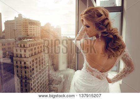 Beautiful Young bride in wedding dress posing near window