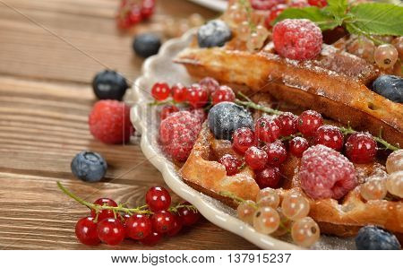 Waffles with berries on a brown background