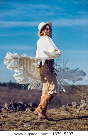 Happy country woman enjoying nature in mountains wearing poncho hat and sunglasses