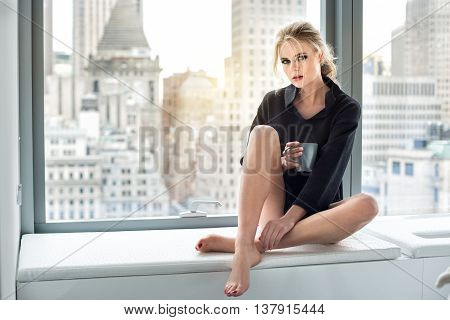 Beautiful woman drinking coffee at the mornig in luxury city penthouse