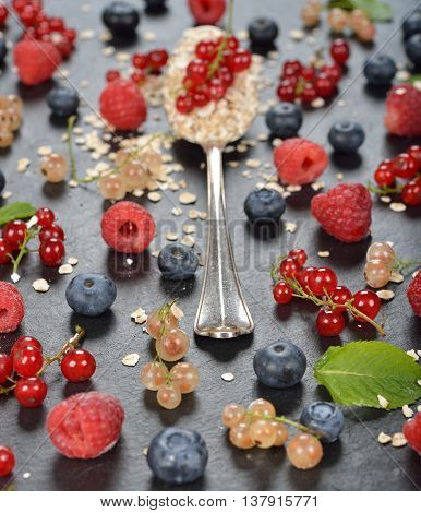 Muesli in a spoon and a variety of berries healthy food concept