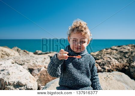 Portrait of blonde kid with windy hair blowing soap bubbles against of seascape