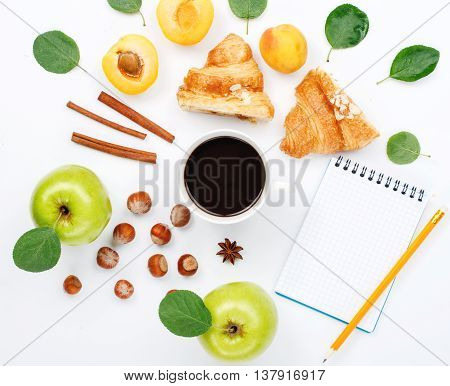 cup of black coffee with sketchbook croissants green apples with leaves hazelnuts and apricots. Cup of coffee with sketchbook and different ingredients for a healthy breakfast. Flat lay top view