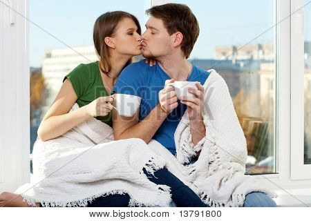 Close-up of young man and woman touching cup together