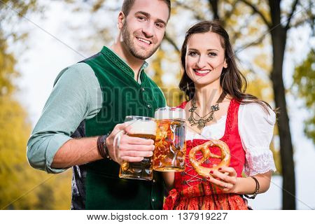 Bavarians in Tracht with Beer and Pretzel in autumn