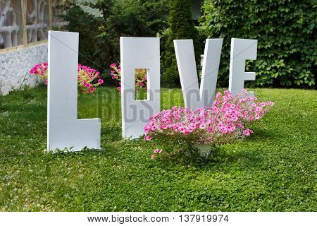 Love word outdoors. Big white plastic letters on the grass near flowers in the garden, wedding ceremony decoration, romantic holiday decor.