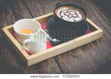 hot coffee with foam milk art. Black cup of coffee. Hot coffee in afternoon break. coffee mocha on the wood desk. Coffee break.(selective focus vintage effect)