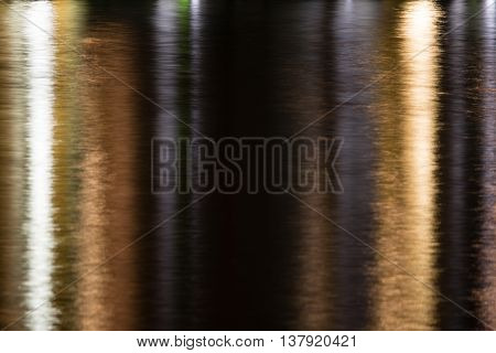 Reflection of yellow and white city lights shimmering on water in yellow and silver at night. Long shutter speed yielded soft blur.