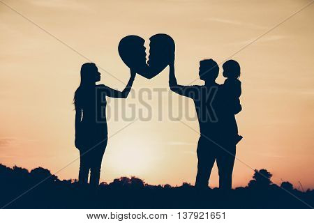 Silhouette of a family comprising a father, mother, and a child having relationship problem / Family problem concept