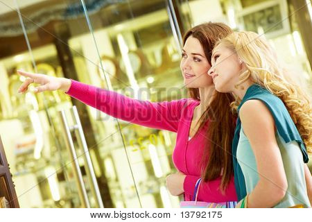 Una mujer apuntando a algo para mostrar su amiga
