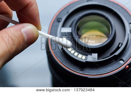 Hand using a cotton swab to clean camera lens contacts / Digital camera maintenance concept